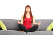 Young female meditating seated on a couch