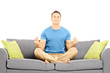 Young male meditating seated on a couch
