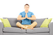 Young man meditating seated on a sofa