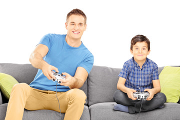 Two brothers seated on a sofa playing video game
