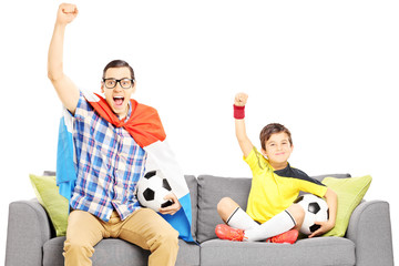 Two male sport fans sitting on a sofa and watching sport