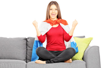 Young female sport supporter sitting on a modern couch cheering