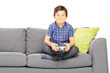 Young smiling kid seated on a sofa playing video game