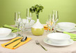 Table setting in green and yellow tones on color  background