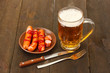 Beer and grilled sausages on wooden background