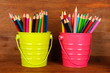 Colorful pencils in two pails on wooden background
