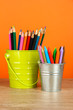 Colorful pencils in two pails on table on orange background