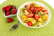Useful fruit salad of fresh fruits and berries in bowl
