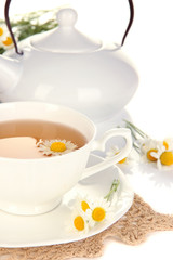 Cup of herbal tea with camomiles close up