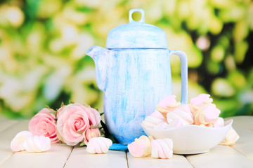 Antique white teapot on wooden table on natural background