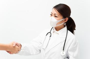 患者と握手している白衣の看護婦
