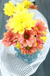 Chrysanthemum flowers in vase on wooden table close-up