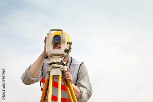 Surveyor engineer making measure with cloud background
