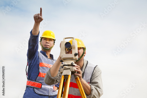 Surveyor engineer making measure with partner