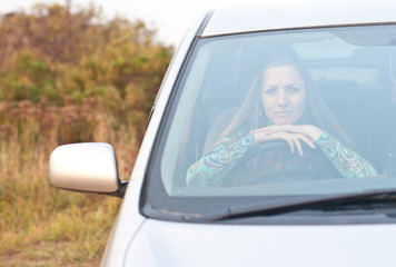 young woman is sitting in the car