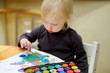 Cute toddler girl drawing with paints in preschool