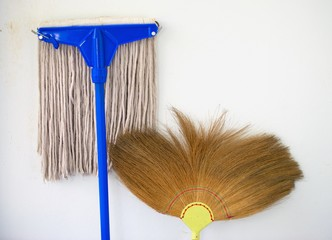 mop and broom propped against a wall