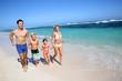 Family running on a sandy beach