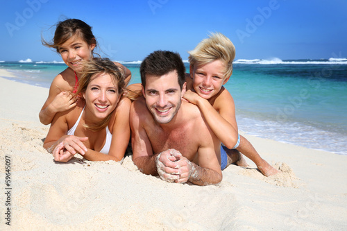 Portrait of happy family laying on the beach