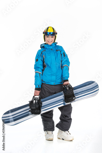 Attractive female snowboarder posing with snowboard.