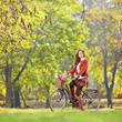 Beautiful female on a bicycle in a park looking at camera