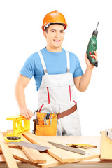 Male manual worker holding a hand drilling machine in a workshop