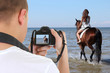 man with camera taking picture of beautiful woman on the horse