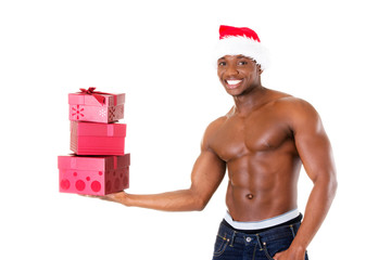 Handsome nude man holding gifts and holding santa hat.