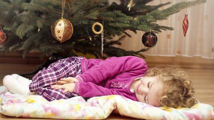 Little girl sleeping under the christmas tree