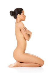 Attractive naked woman sitting on knees. Side view.