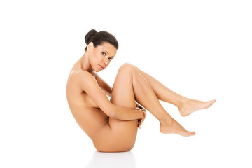 Beautiful naked woman in a crouch, holding her knees.