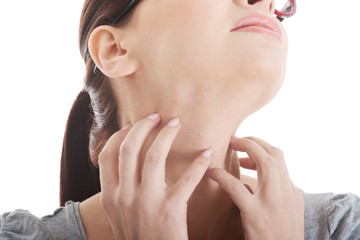 Young woman is scratching her neck.