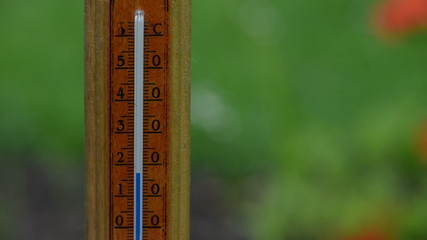 Fast rising temperature on wooden outdoor thermometer scale