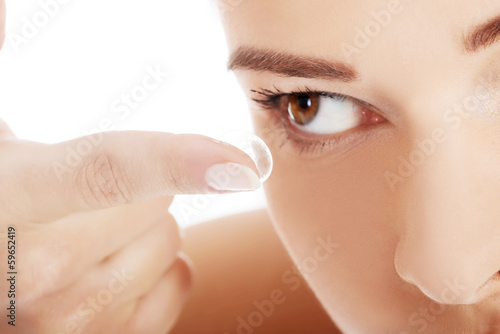 Close up on woman putting lens into eye.