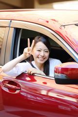 車の前でピースする女性