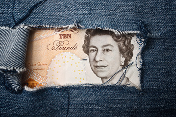 Ten pounds bill through torn blue jeans texture