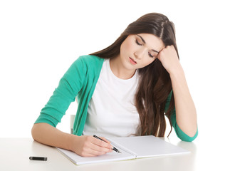 Young casual woman writing in workbook.