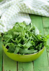 bowl of green salad with arugula on wooden table