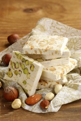 white nougat with different nuts on a wooden table