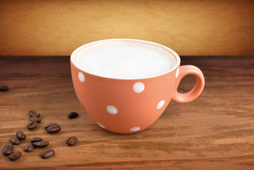 A cup of coffee on a wooden background. coffee beans