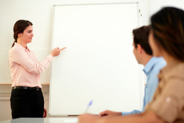 Pretty young businesswoman pointing at whiteboard