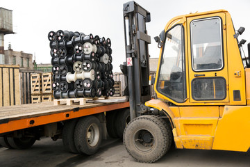 Forklift stacker loading cargo with pallet on truck trailer