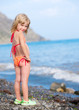 Small child girl standing on the beach