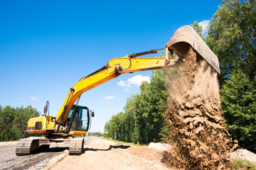 Excavator unloading sand during road construction works