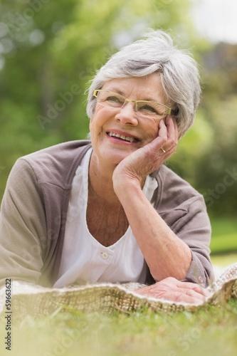 Smiling senior woman lying at park