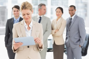 Businesswoman using her tablet with team behind her
