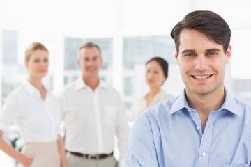 Smiling businessman standing with team behind him