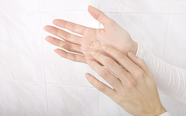 Hands applying sanitizer gel