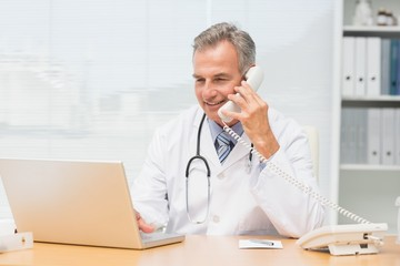Doctor using laptop and talking on phone at desk