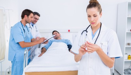 Doctor holding a syringe with colleagues and patient in hospital